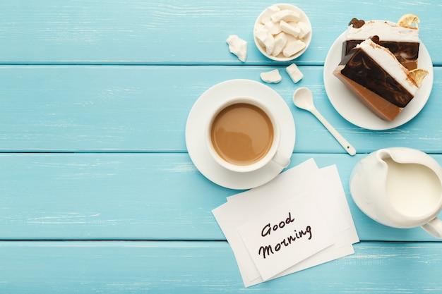 Tazza di caffè con pezzi di torta e nota buongiorno sul tavolo rustico blu dall'alto. vista dall'alto su una colazione accogliente e gustosa, copia spazio