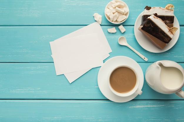 Tazza di caffè con pezzi di torta e note di carta sul tavolo rustico blu dall'alto. vista dall'alto su una colazione accogliente e gustosa, copia spazio