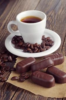 Tazza da caffè con cioccolatini su tavola in legno rustico