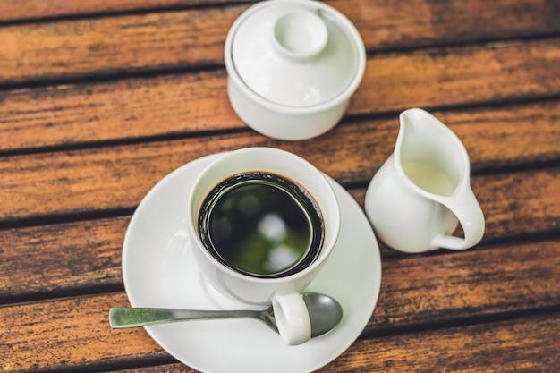 Tazza di caffè sulla tavola di legno nella caffetteria tono vintage