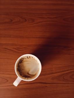 Tazza di caffè sulla scrivania in legno, sfondo piatto laici e mockup di affari, vista dall'alto