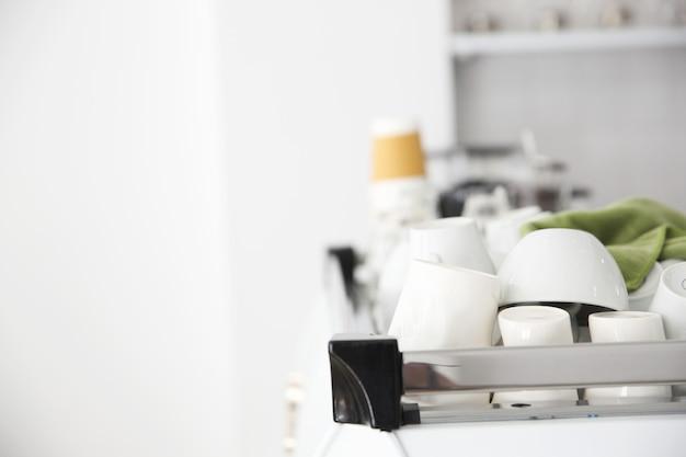Tazzine da caffè sulla macchina da caffè in coffeeshop bianco