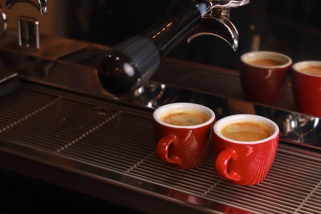 Le tazze da caffè stanno all'interno della macchina da caffè su una griglia, il caffè fresco viene versato all'interno delle tazze