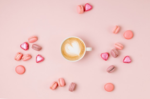 Tazze da caffè con caramelle e amaretti su sfondo rosa pallido pale