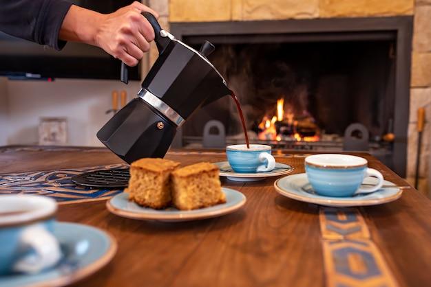 Tazze da caffè con caffettiera e caminetto acceso