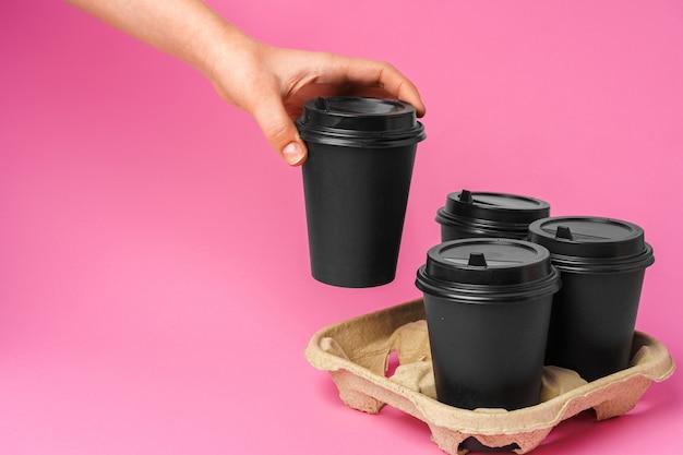 Consegna del caffè. mano umana che tiene tazza di caffè da asporto su sfondo di carta