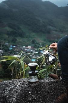 Gocciolare il caffè su una montagna in un villaggio rurale, versare acqua calda