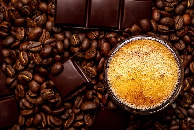 Caffè in una tazza di vetro su un tavolo di legno. chicchi di caffè e pezzi di cioccolato.