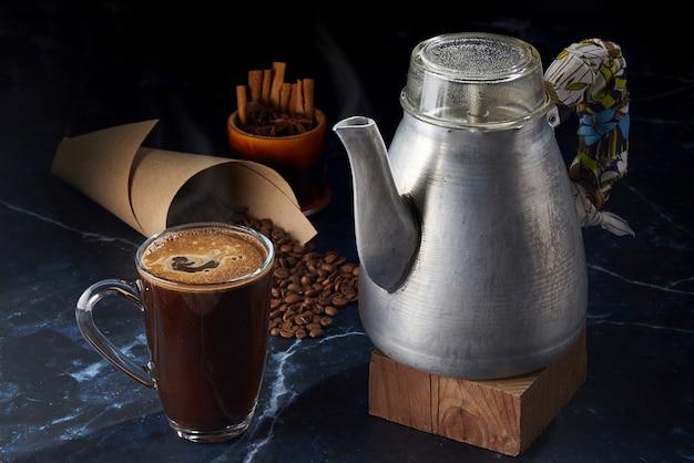 Caffè in una tazza di vetro e una caffettiera geyser in alluminio vintage su uno sfondo scuro con chicchi di caffè