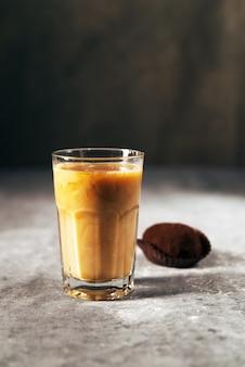 Caffè in un bicchiere con latte e biscotti al cioccolato su un muro grigio scuro grunge e struttura