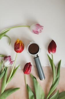 Porta caffè dalla macchina del caffè e tulipani freschi su sfondo bianco
