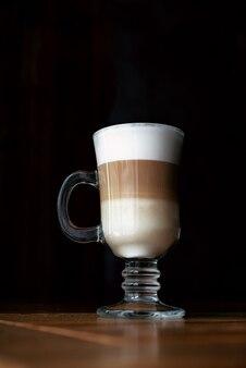 Latte al caffè in una tazza di vetro con sfondo nero