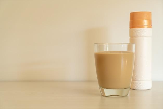 Bicchiere di caffè latte con bottiglie di caffè pronte da bere sul tavolo