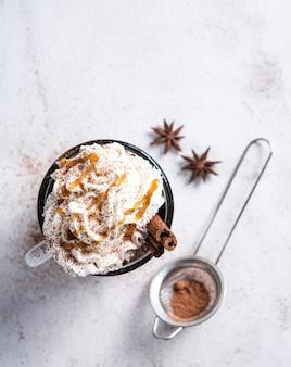 Latte al caffè con crema al caramello cremoso e cannella in una tazza bianca su un tavolo bianco. vista dall'alto e copia spazio