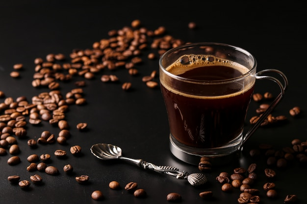 Caffè in una tazza leggera su uno sfondo scuro con chicchi di caffè sparsi sul tavolo, orientamento orizzontale