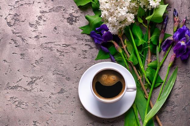 Fiori di caffè e lilla su una superficie di cemento grigio