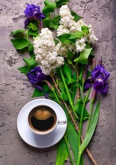 Fiori di caffè e lilla sul tavolo di cemento grigio
