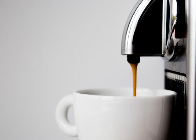 Macchina per il caffè e tazza vuota pronta per la bevanda di versamento sul quadrato bianco del fondo della parete