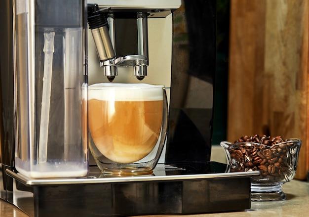 La macchina da caffè produce cappuccino in una tazza trasparente.