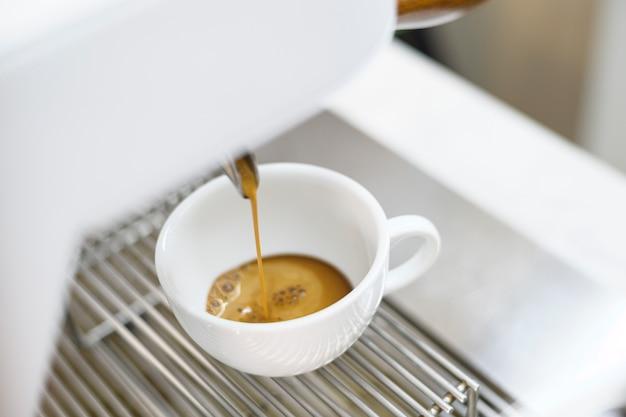 Macchina da caffè che produce caffè nero e versa in una tazza al caffè