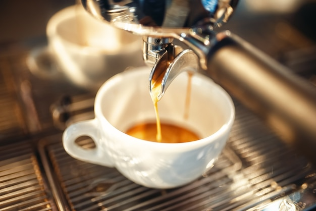 La macchina del caffè versa la schiuma nel primo piano della tazza