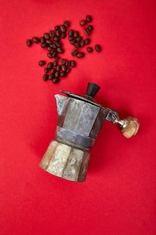 Macchinetta del caffè e chicchi di caffè sul fondo rosso di tendenza