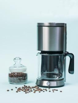 Caffettiera e vaso di vetro con chicchi di caffè su sfondo blu. il concetto di una colazione classica.