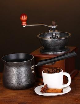Caffettiera con macinacaffè e tazza bianca sulla tavola di legno