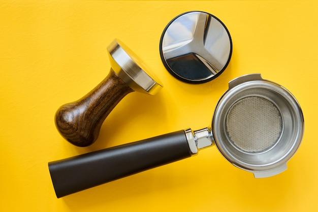 Strumenti per la preparazione del caffè, supporto per cestello del caffè, appiattimento e manomissione su sfondo giallo