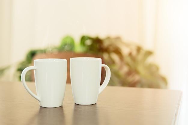 Caffè al mattino, due tazza di tè bianco tazza posizionata sul tavolo di legno a casa.