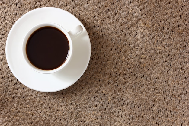 Caffè in una tazza e piattino sulla tovaglia di tela. vista dall'alto.