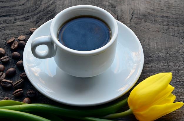 Tazza da caffè con fiore tulipano giallo e chicchi di caffè