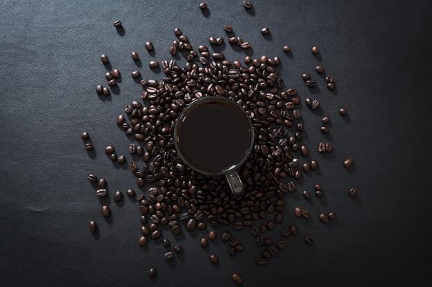 Tazze da caffè e chicchi di caffè sono posti sulla scrivania
