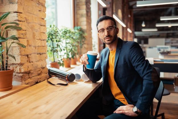 Caffè vicino alla finestra. bell'uomo barbuto con gli occhiali che beve caffè seduto vicino alla finestra