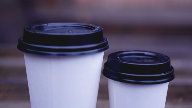 La tazza del mestiere di carta del caffè si erge su una superficie di legno su uno sfondo sfocato. posto per testo o logo.