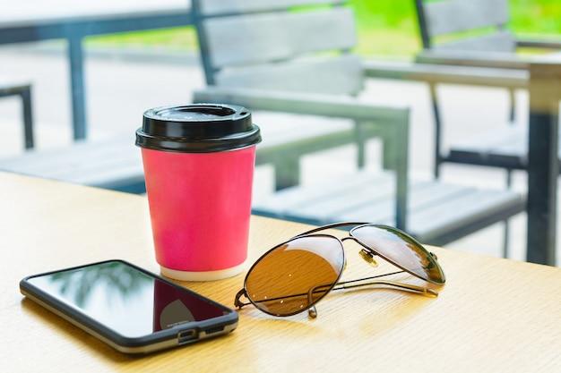 Caffè, telefono ed occhiali da sole sulla tavola marrone in caffè sulla strada con l'interno esterno