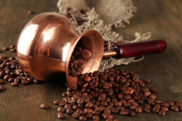 Caffettiera con chicchi di caffè sul tavolo di legno
