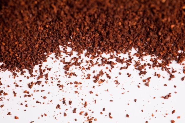 Polvere di caffè (caffè macinato), tavolo bianco.
