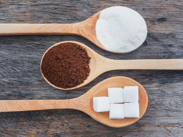 Caffè e latte in polvere con cubetti di zucchero sul cucchiaio di legno