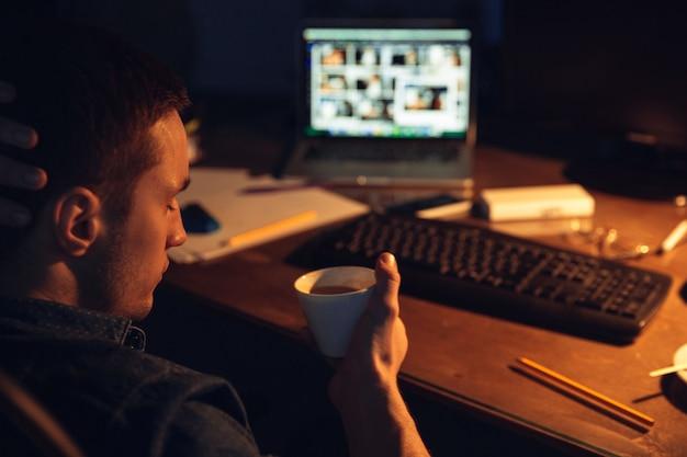 Il caffè salva. uomo che lavora in ufficio da solo durante la quarantena del coronavirus o del covid-19, rimanendo fino a tarda notte. giovane uomo d'affari, manager che svolge attività con smartphone, laptop, tablet in un'area di lavoro vuota.