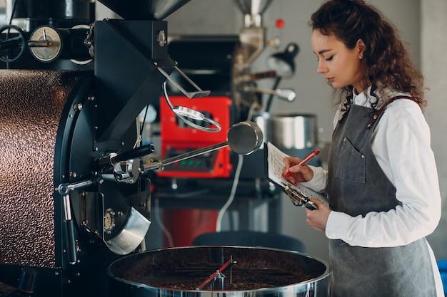 Macchina per la torrefazione del caffè e donna barista con penna per scrivere tablet durante il processo di torrefazione