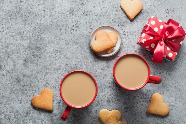 Caffè servito per coppia, biscotti fatti in casa e regalo sul tavolo grigio. biglietto di auguri di san valentino. vista dall'alto. spazio per il testo.