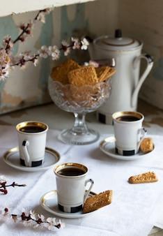 Caffè servito con biscotti di pasta frolla e dolci sullo sfondo di rami fioriti e un vecchio armadio.