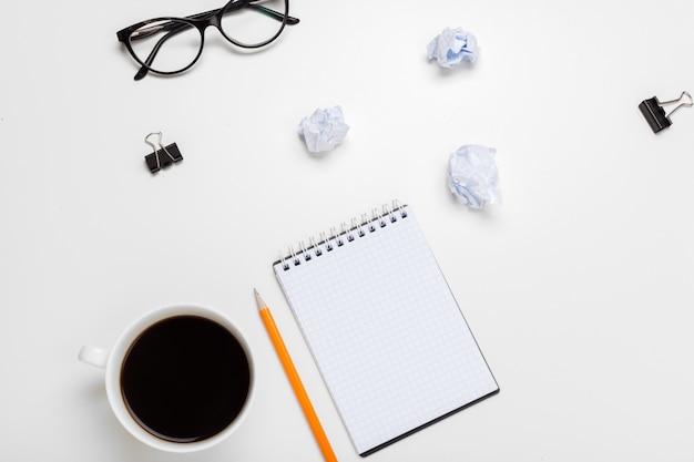 Caffè, fogli di carta e batuffoli stropicciati sul tavolo