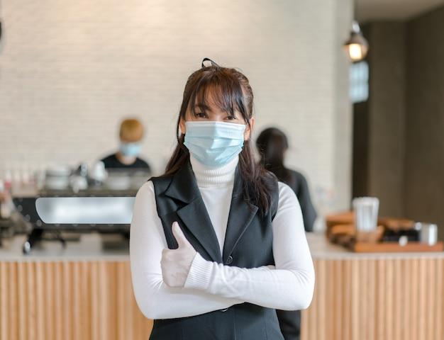 Imprenditore della caffetteria indossando mascherina chirurgica. fiduciosa donna d'affari