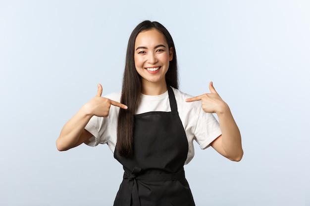 Caffetteria, piccola impresa e concetto di avvio. amichevole barista asiatico sorridente, impiegato del ristorante in grembiule nero che si indica, vantandosi. il miglior barista in mostra in città