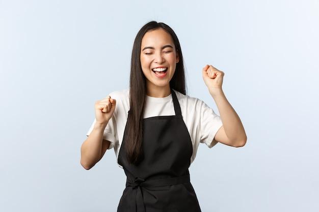 Caffetteria, piccola impresa e concetto di avvio. esultanza soddisfatta pompa pugno barista femminile. personale asiatico del caffè in grembiule nero che celebra la vittoria, trionfa e urla sì eccitato