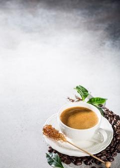 Superficie del caffè con appena preparato in una tazza bianca con fagioli e foglie. copia spazio