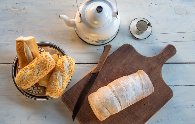 Tavolino con pane, teiera e tazza di caffè e un coltello, luce naturale, su un tavolo bianco, vista dall'alto