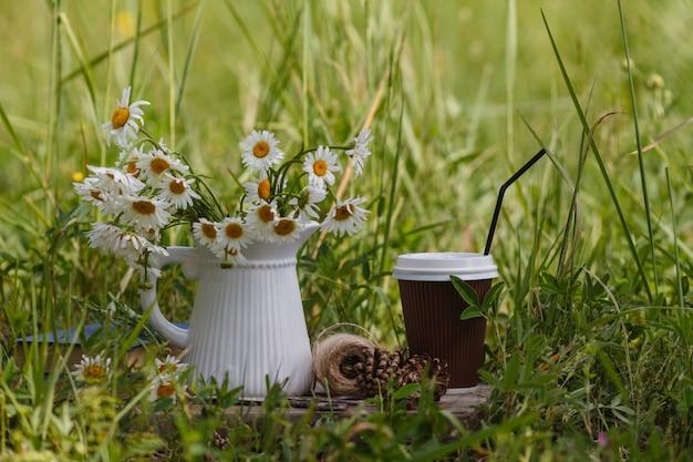 Caffè da asporto, fiori di camomilla e libri.